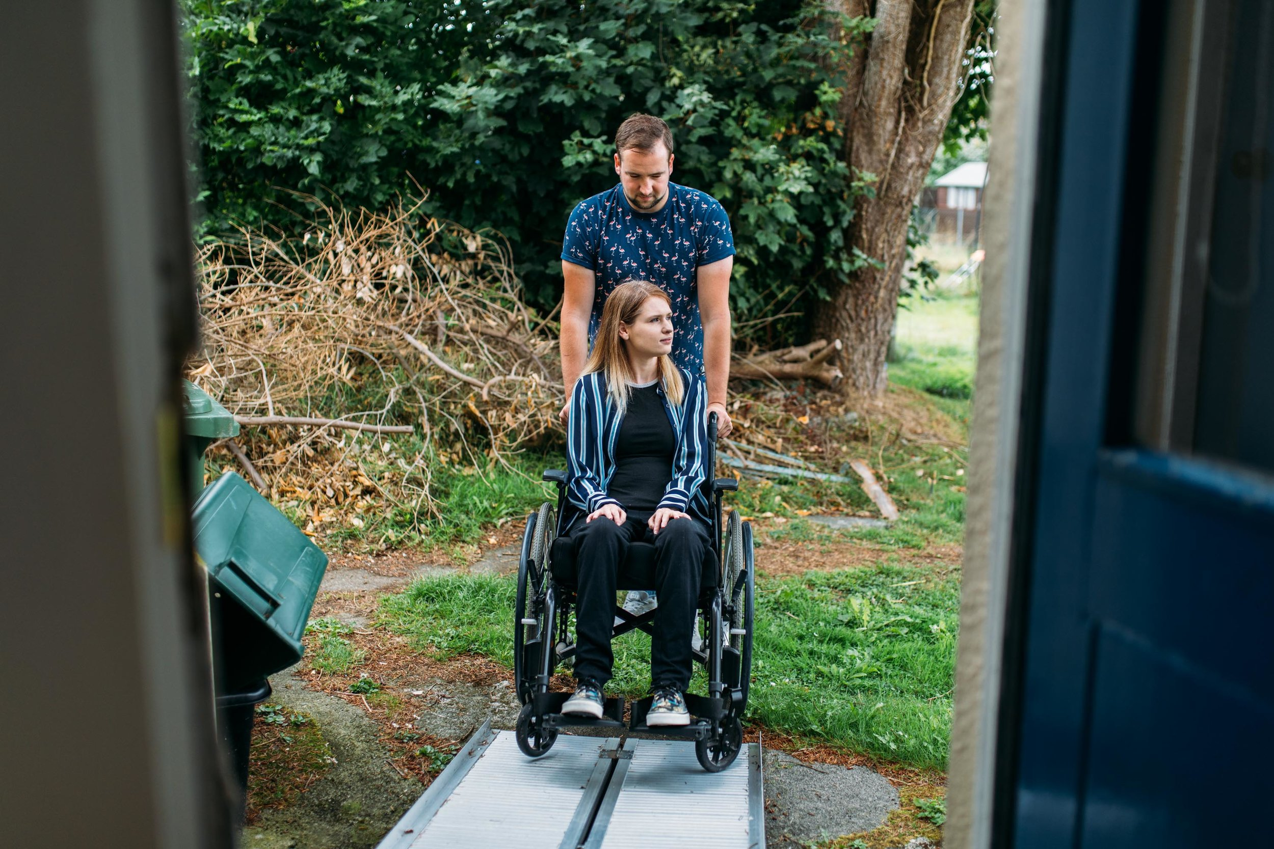 Kay Garner's partner Ryan Waters pushes her up the temporary ramp in the back garden of their council-provided home. She uses the ramp to get in and out of the house through the kitchen as she can not use the front door. They were forced to move out of their inaccessible previous home after Kay's spinal injury. Penzance, Cornwall. 20th Aug 2018.