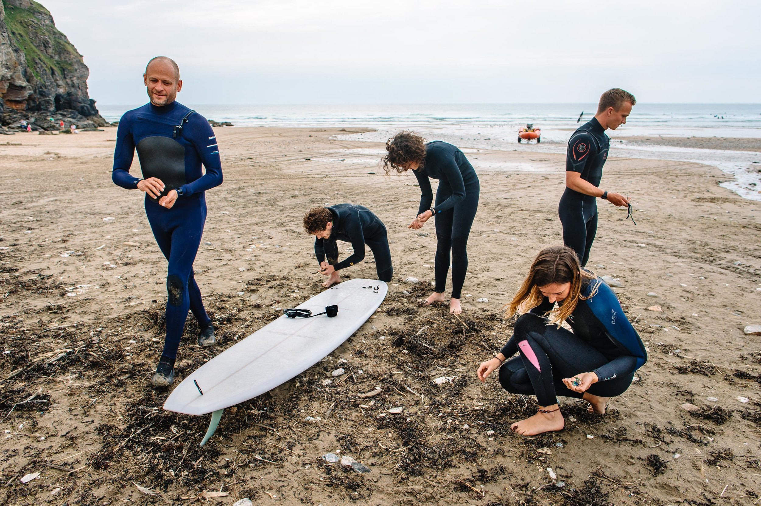 Chief Executive of Surfers Against Sewage, Hugo Tagholm, and employees Dominic Ferris, Ellie Ewart, Sally Fish and Harry Dennis (left to right) collect pieces of plastic pollution and other litter along Porthtowan Beach. St Agnes, Cornwall, UK. 29 May 2018.