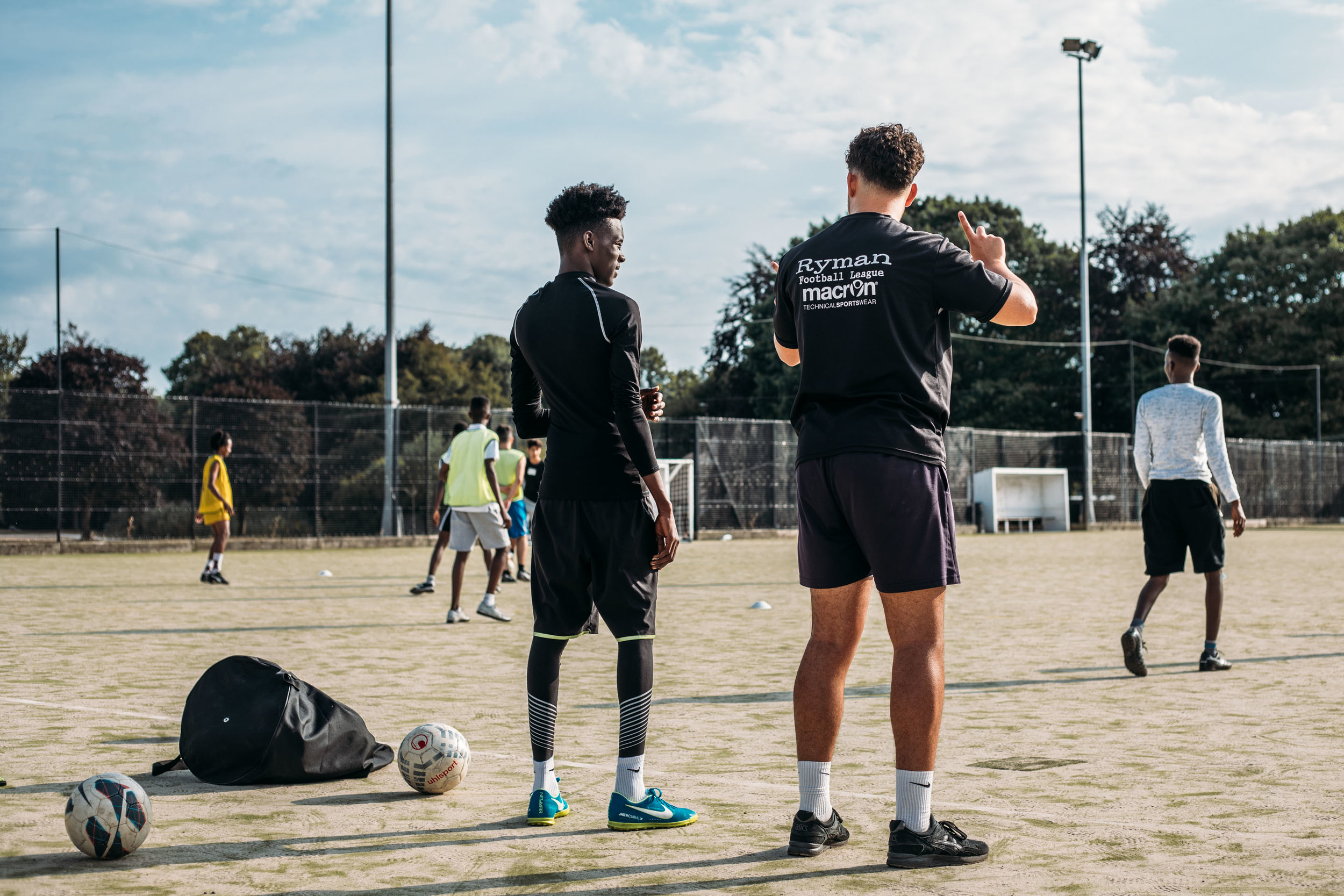 Volunteer coach Joss Hole talks offside with a Nations United FC player on Chichester University football pitch. Nations United FC is a football team made up entirely of refugees - set up earlier this year by volunteer group Sanctuary in Chichester. The team has players from around 8 nationalities and was started to help integrate young refugees in West Sussex into the community. 20th July 2018.