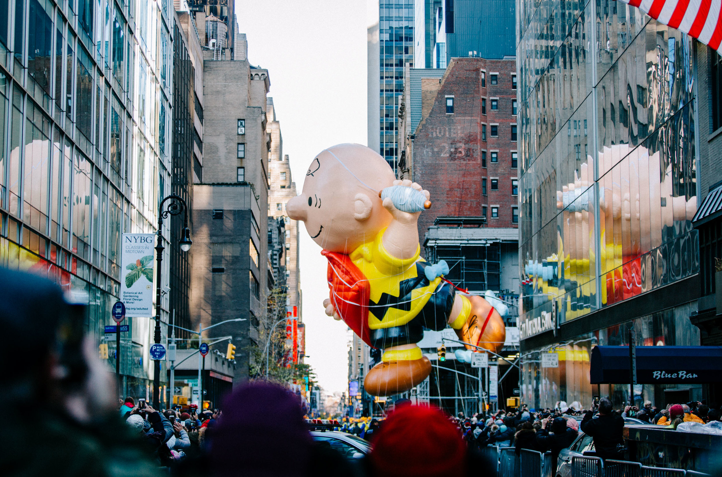 Onlookers watch as the Charlie Brown float glides past the Manhattan skyscrapers during the Macy's Thanksgiving Day Parade. New York, USA.. 23rd Nov 2017