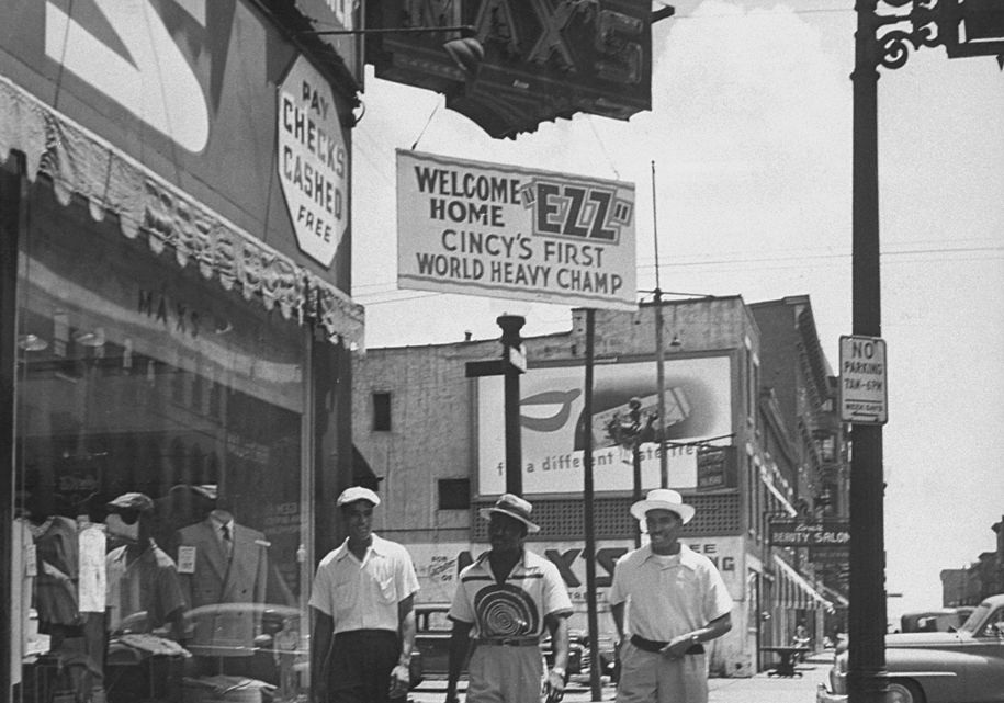 Heavyweight boxing champ Ezzard Charles walking between 2 friends below sign reading: WELCOME HOME EZZ - CINCY'S 1ST WORLD HEAVY CHAMP, through city streets of Cincinnati. (Photo by Norman J. Gordon/Pix Inc./The LIFE Images Collection/Getty Images)