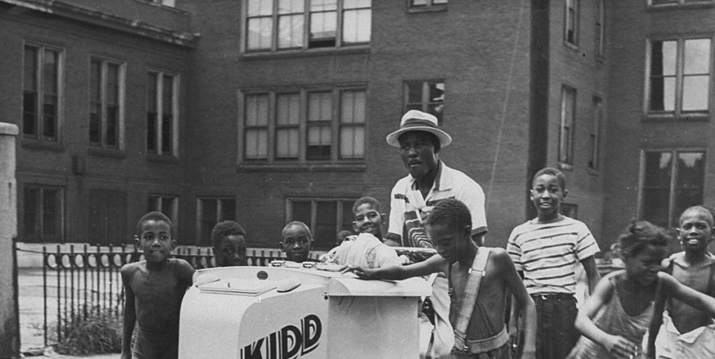 Heavyweight boxing champ Ezzard Charles pushing ice cream cart as group of local black youths follow him in city streets, during visit to hometown. (Photo by Norman J. Gordon/Pix Inc./The LIFE Images Collection/Getty Images)