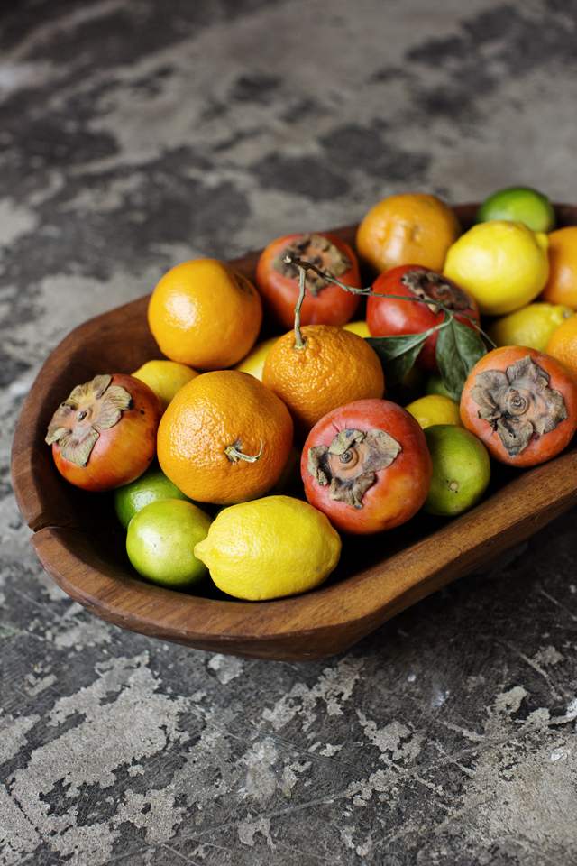 Lemons, limes, persimmons and oranges in a wooden bowl | Young Joni | The Restaurant Project