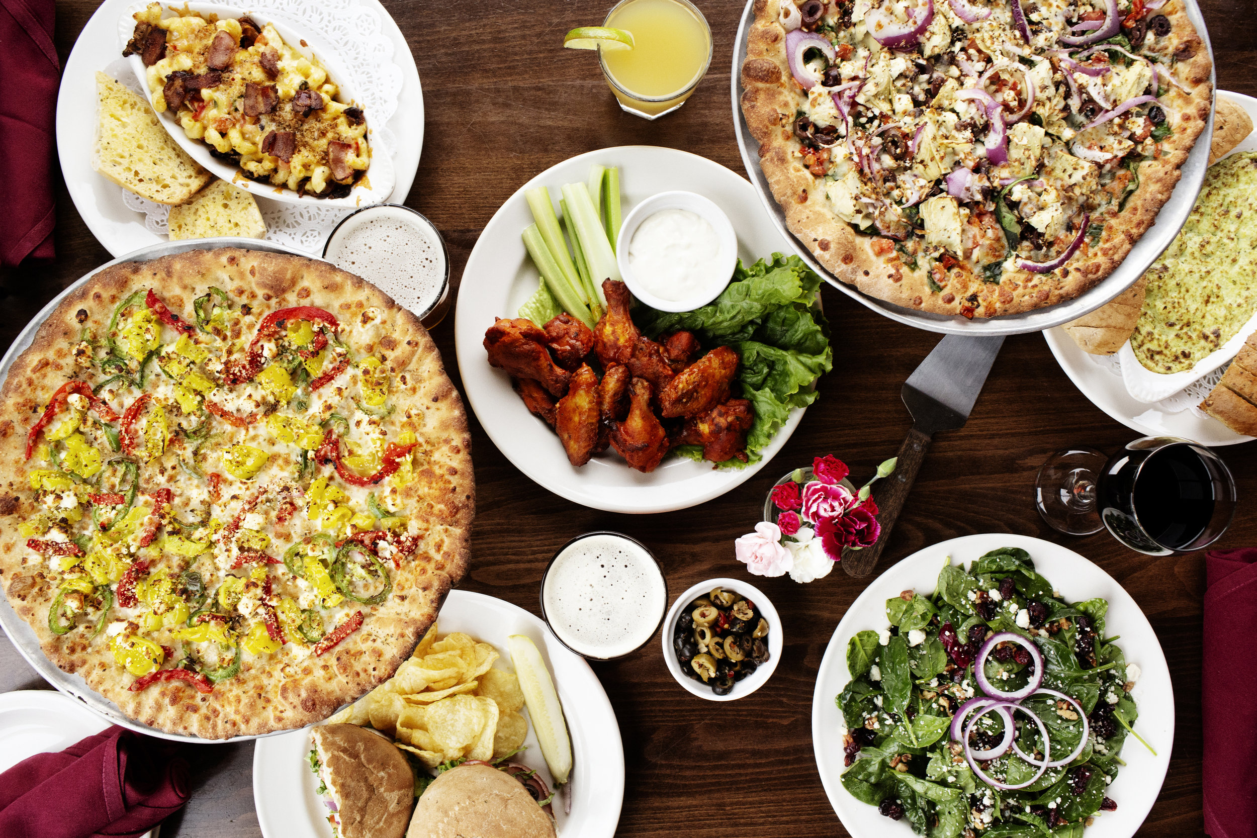 A table full of pizza, salad and appetizers | Pizza Lucé | The Restaurant Project