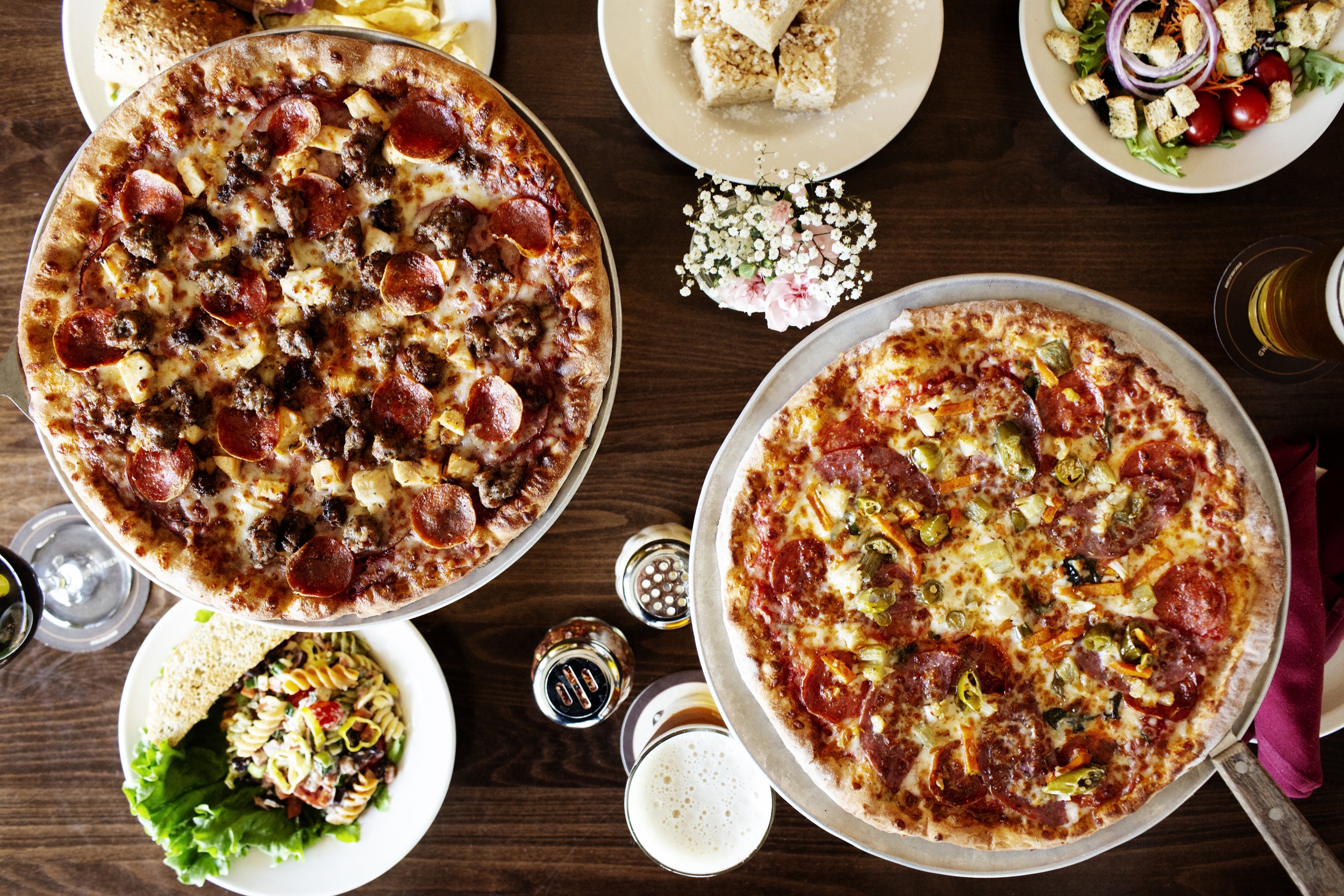 A table full of pizzas, salad and pasta  | Pizza Lucé | The Restaurant Project