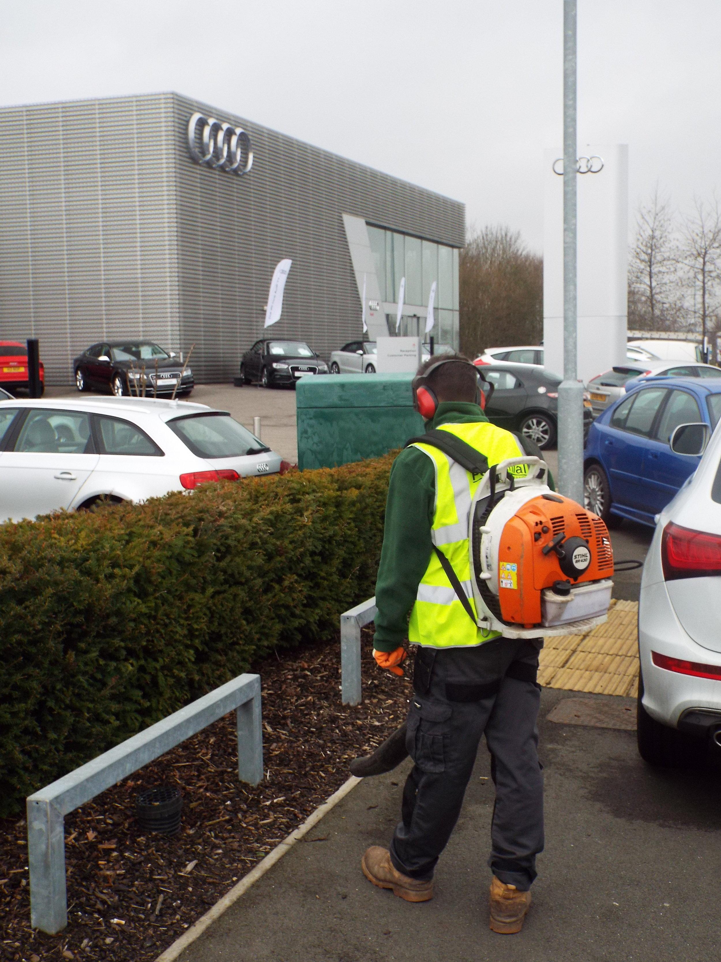 Man using a leaf blower at a car dealership