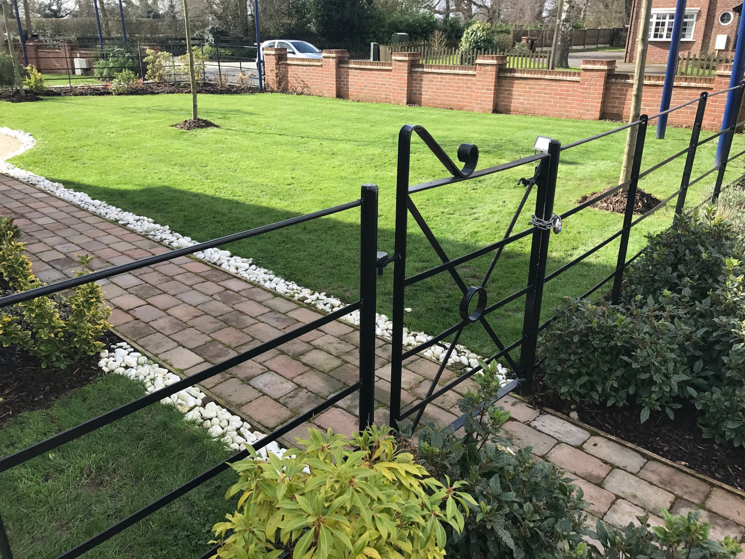 Block paved garden path and black gate