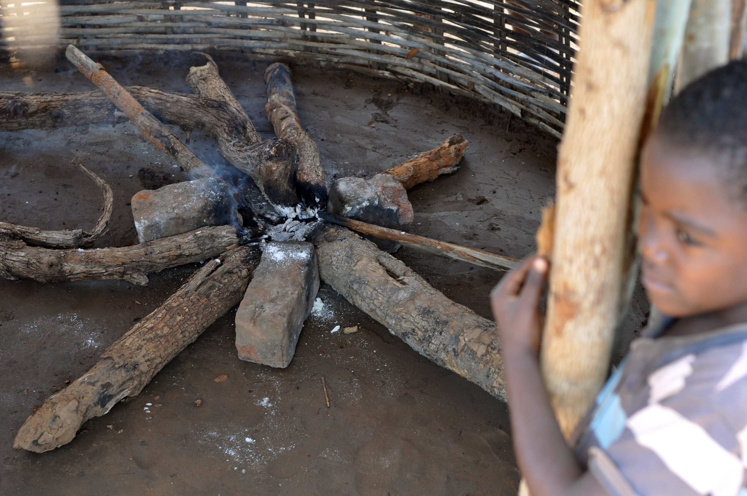 Open fires utilize large logs, which are unsustainably harvested from surrounding forests and wooded areas of agricultural lands, the major driver of deforestation in the Luangwa valley region of Zambia. Three-stone fires like this one are less than 10% efficient in transferring the energy in the wood into the pot to cook food in addition to being very smoky.