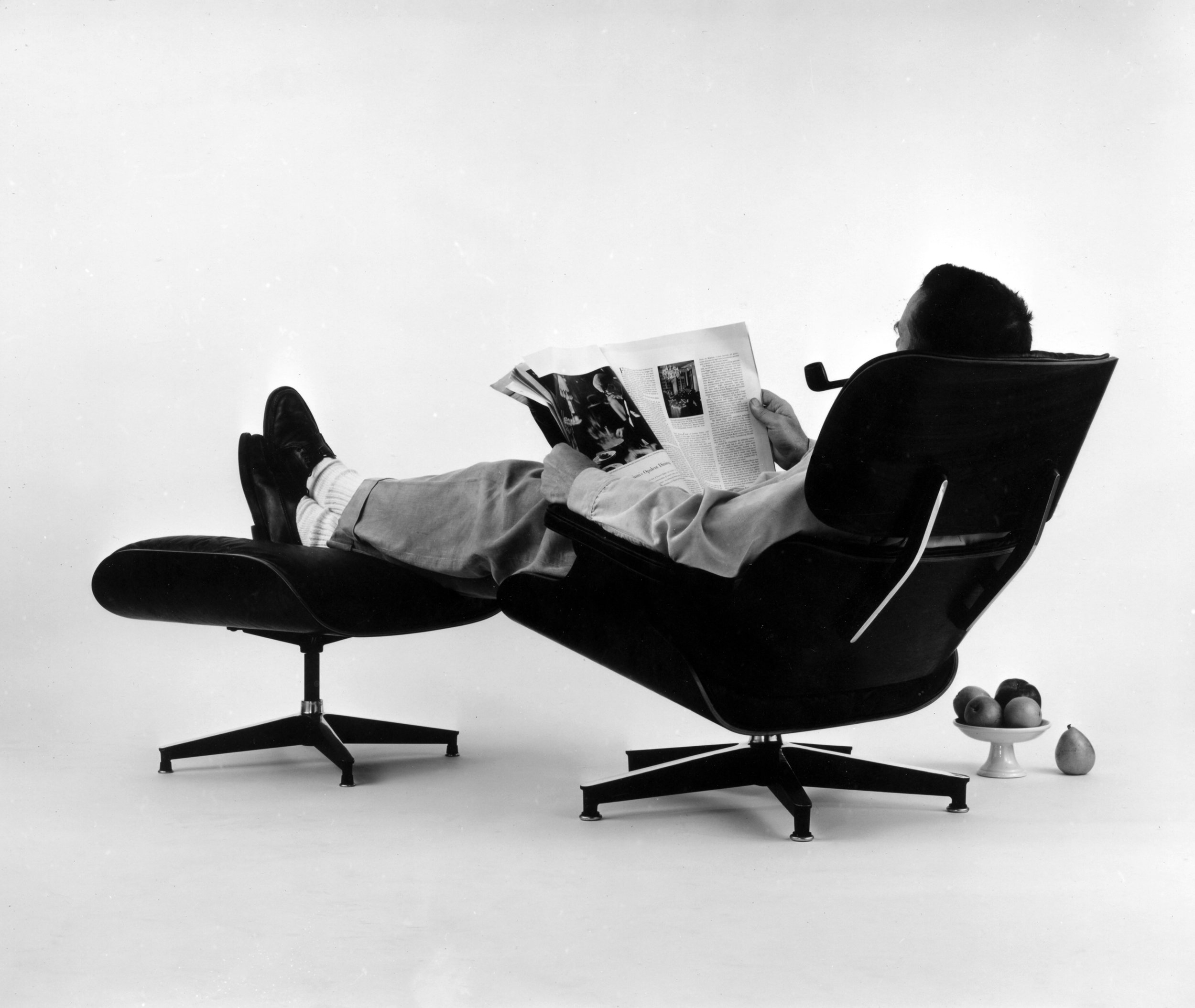 An Eames Celebration. Charles Eames posing in the Lounge Chair, photo for an advertisement, 1956.© Eames Office LLC