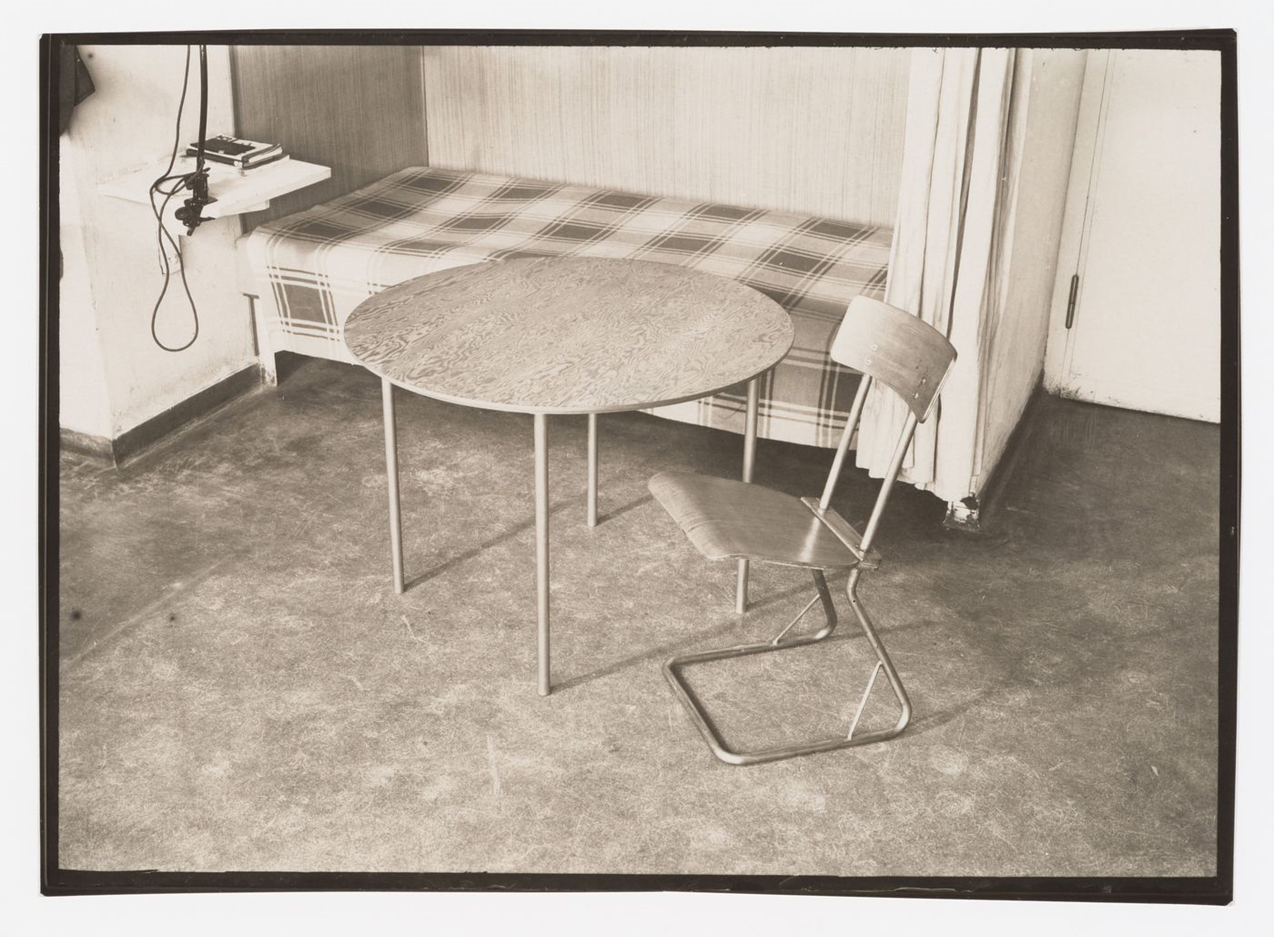Interior view of a studio apartment in the Bauhaus building showing a bed, round table and side chair designed by Marcel Breuer, Dessau, Germany — Collection Centre Canadien d'Architecture/Canadian Centre for Architecture, Montréal