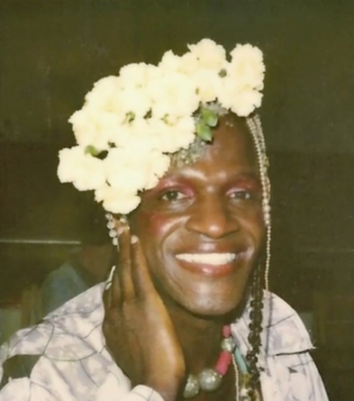 A photo of a black woman wearing pink eyeshadow, pink blush, orangey-red lipstick, a white flower crown, and a silver and pink bead necklace. She smiles widely and rests a hand on her cheek.