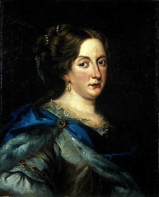 """The painting """"Christina of Sweden"""" by Jacob Ferdinand Voet. It features a portrait of Christina, a white woman with brown hair pulled back with gold pieces. She wears a green and blue dress with gold details, gold earrings, and red lipstick. She smiles just slightly and stares at the viewer with dark eyes. Her cheeks and nose are flushed pink."""