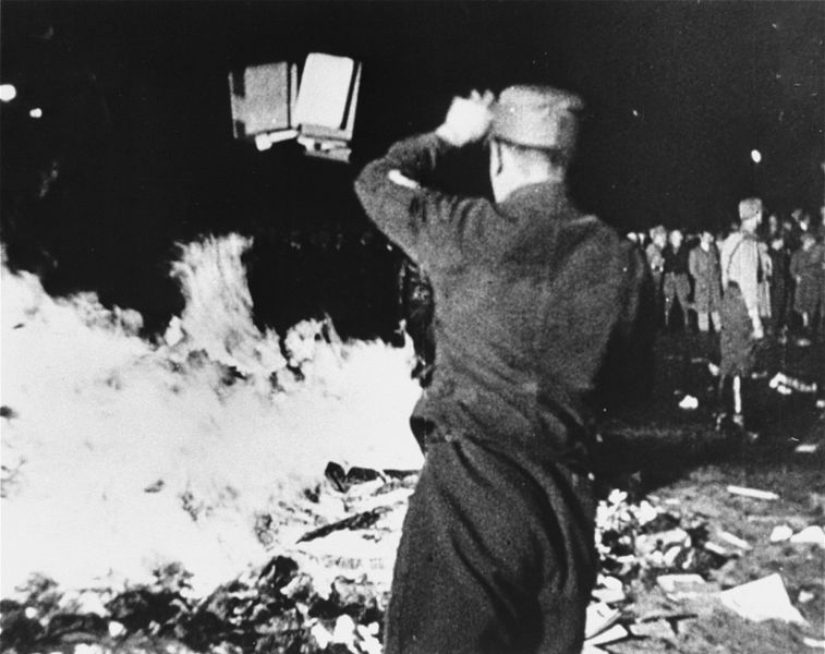 A group of Nazis throw documents and books into a fire in the street.