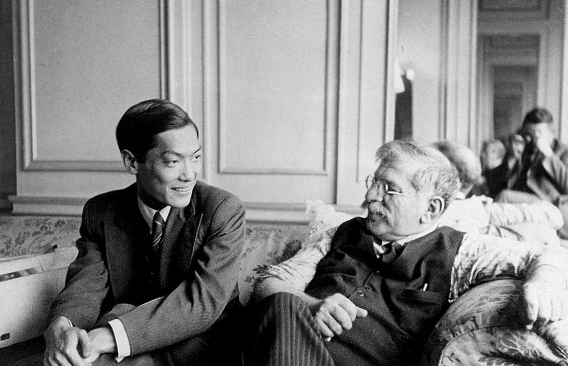 A black and white photo of Li Shiu Tong and Magnus Hirschfeld sitting on a couch in an ornate room at the fourth conference of the World League for Sexual Reform.