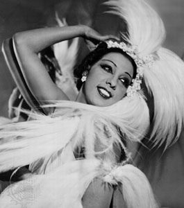 A black and white photo of Josephine Baker, a black woman with short black hair tucked into a large feather and crystal headpiece. She wears crystal earrings and bold makeup, posing and smiling into the distance.