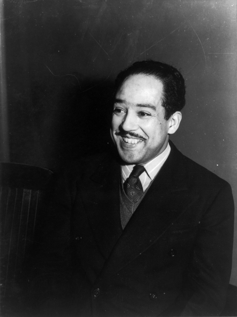 A black and white photo of Langston Hughes, a black man with short hair and a thin mustache. He smiles widely and wears a black suit with a striped shirt, dark sweater, and paisley tie.