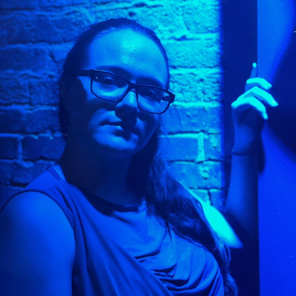 A photo in shades of blue of a person with long, dark hair pulled behind them. They wear dark-rimmed glasses and rest one hand on a nearby wall.