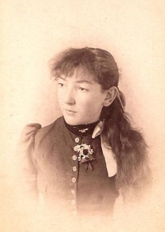 A yellowed black and white photo of Evelyn Irons, a white woman with long dark hair. She has bangs and her hair is tied into a ponytail behind her. She wears a dress with puffy sleeves and many buttons that close at her neck. She wears a medal on her chest and a ribbon around her neck.