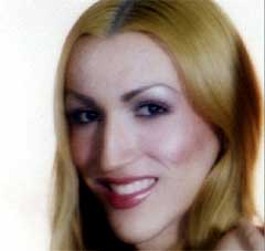 A photo of Victoria Arellano, a Latina trans woman with wavy blonde hair. She smiles widely and wears purple eyeshadow and pink lipstick.