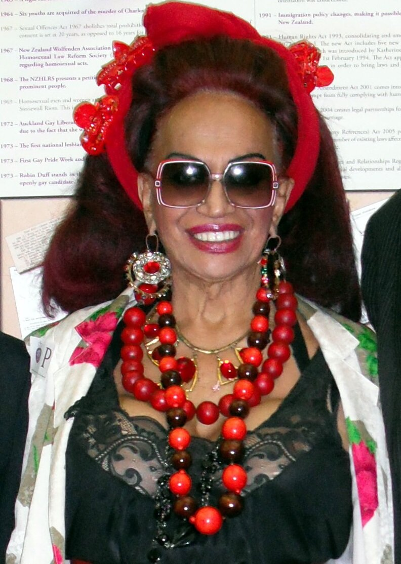 Carmen Rupe, a Māori woman with long brown hair wearing a red headpiece, red bead necklaces, red and white earrings, and sunglasses. She smiles.