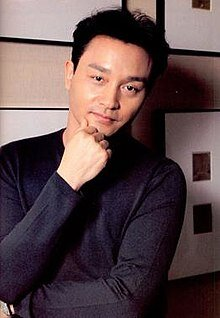 Leslie Cheung looking thoughtfully at the camera with his hand on his chin.