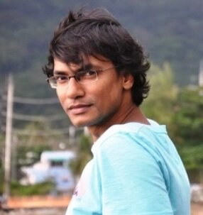 Xulhaz Mannan, a Bangladeshi man with light brown skin and wavy dark brown hair. He wears frameless glasses and a light blue T-shirt.