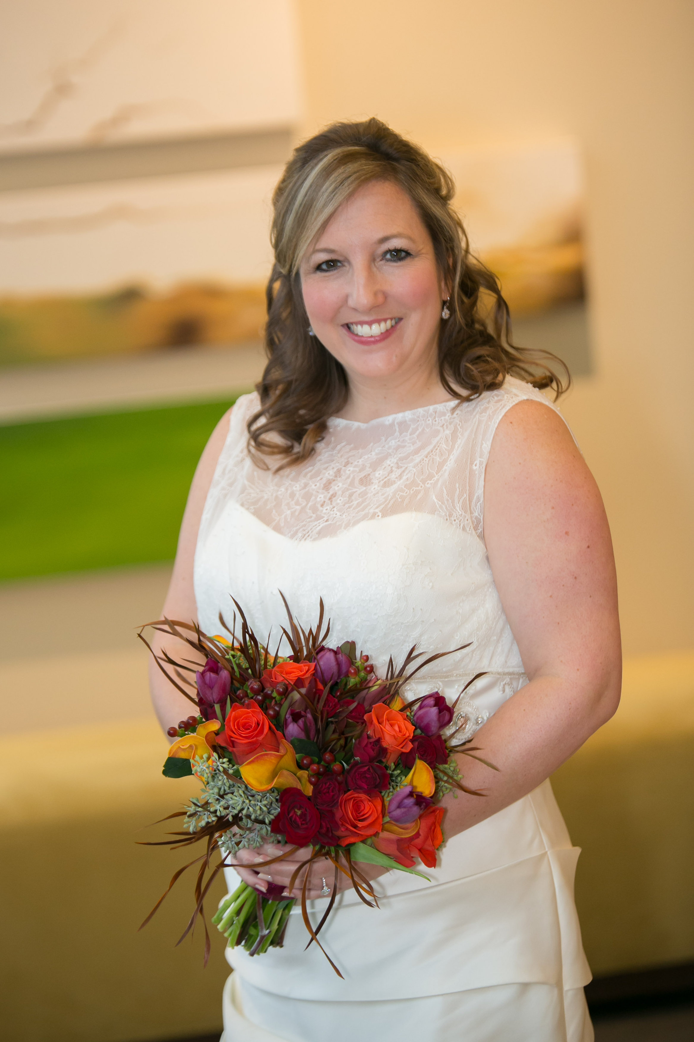 Amy chose a bright mix of fall colors for her and her daughter's bouquets.  The rich orange roses were accented with purple tupils, yellow calla lilies, deep red spray roses, burgundy hypericum berry.  The seeded eucalyptus,sunset leucadendron and feathers completed this impactful mix of flowers.