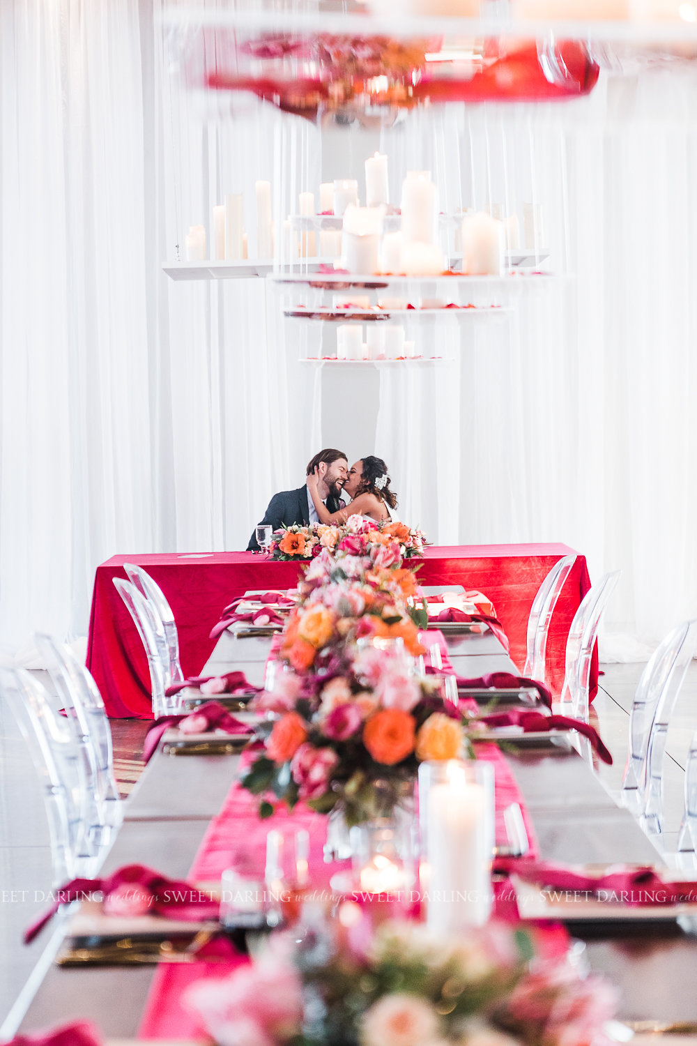 Now that's a feasting table! We suspended acrylic shelves at varying heights above the line of harvest tables, covered them with rose petals and then added candle groupings. Not only did it add a gorgeous glow to the room, but while seated at the tables there was rose petal garden overhead.