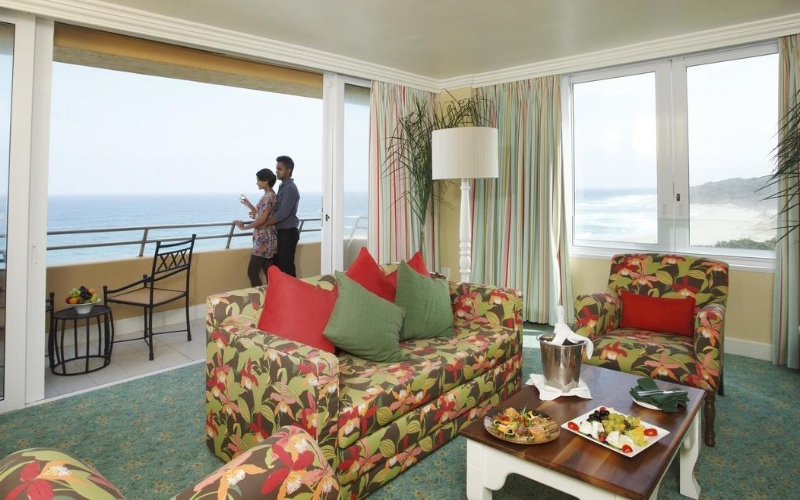 Wild Coast Sun Suite- Presidential Suite-lounge-with couple on the balcony.jpg