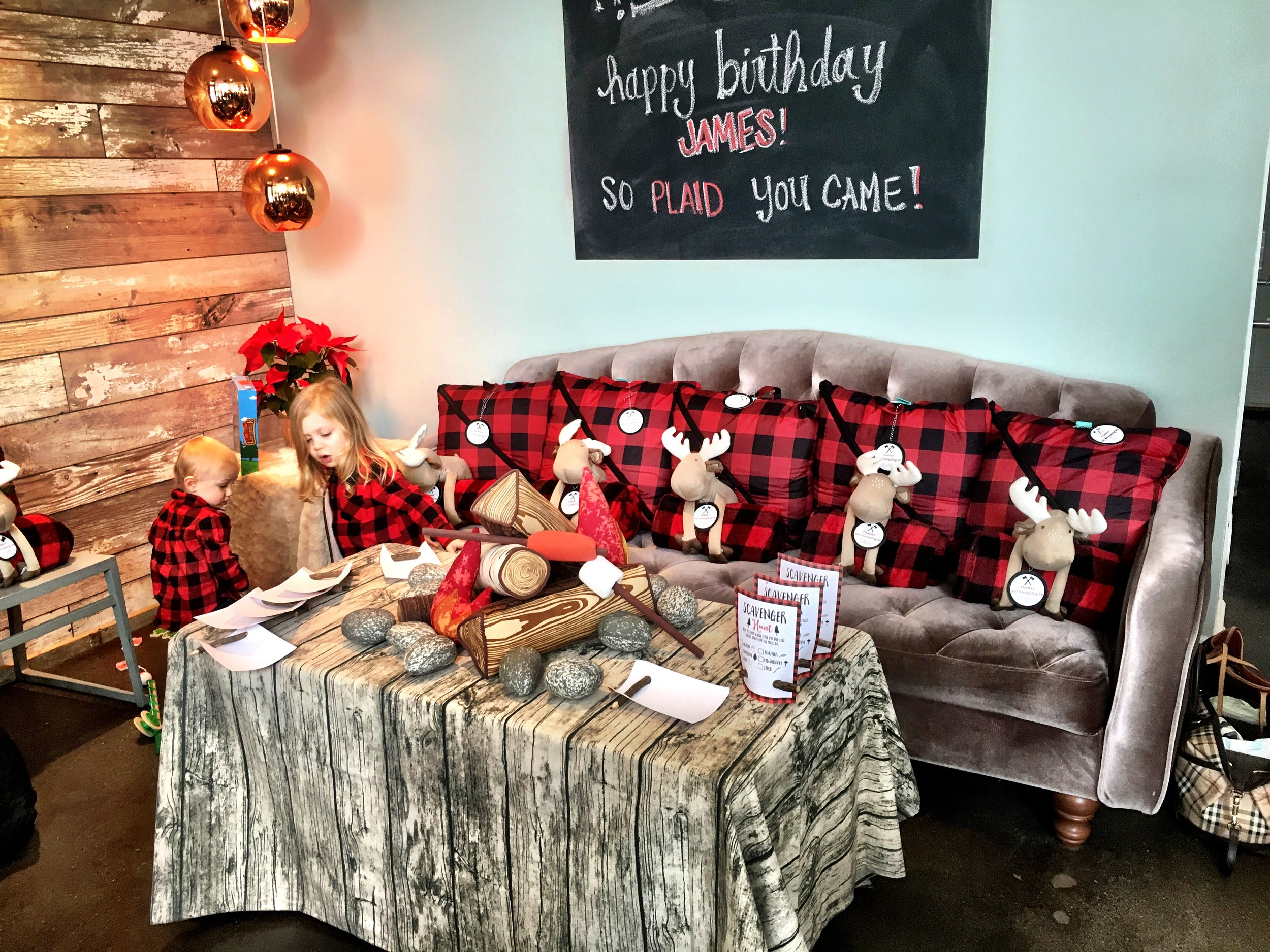 Buffalo check sleeping bags or blankets with a moose for the favors and an activity table complete with a campfire