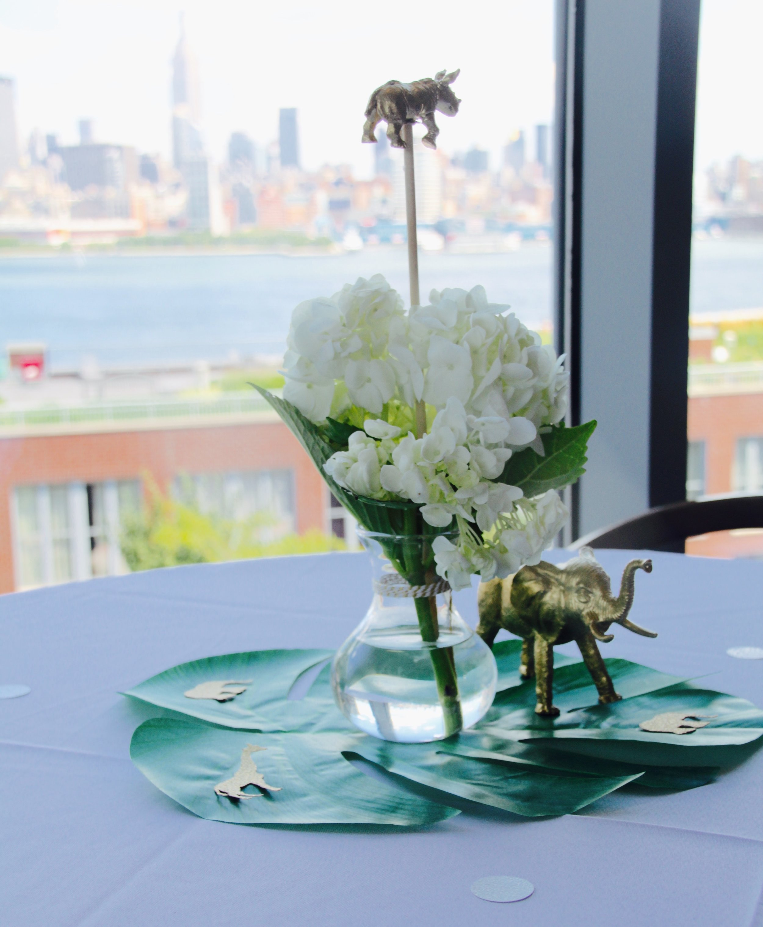 Centerpieces, white hydrangeas, green palms, and gold confetti and animals