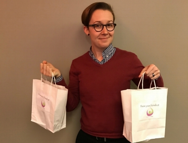 Staff at Circle of Hope partner program holding Dignity Bags full of toiletry donations.