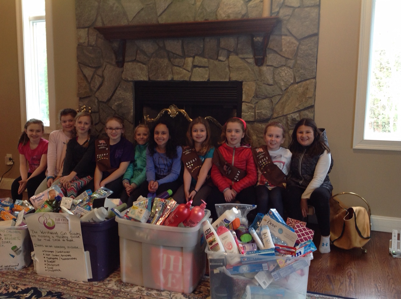 A Girl Scout troop sits with large bins of toiletry donations for Circle of Hope.