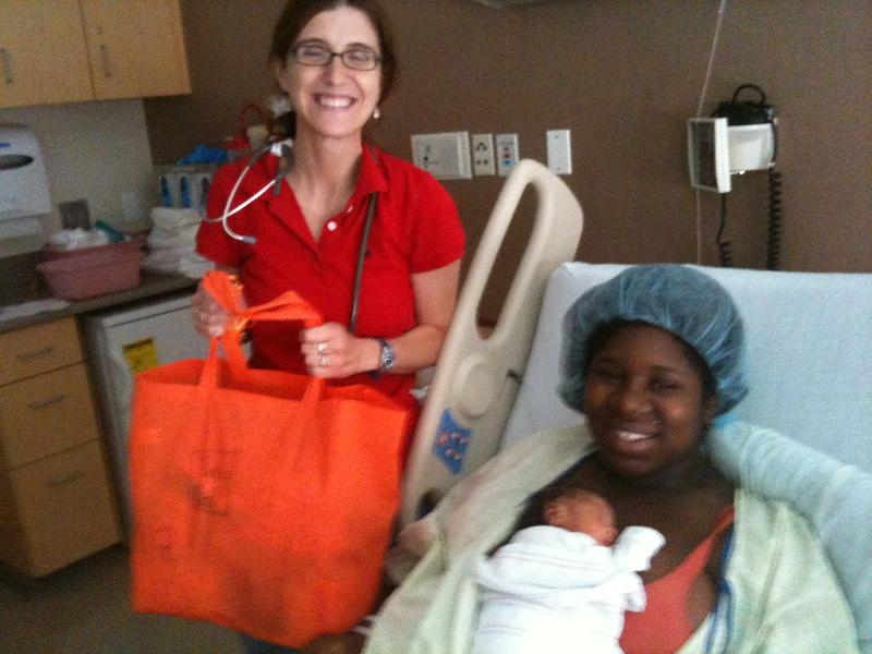 A homeless mother holding her newborn in the hospital receives a Circle of Hope Welcome Baby Bag.