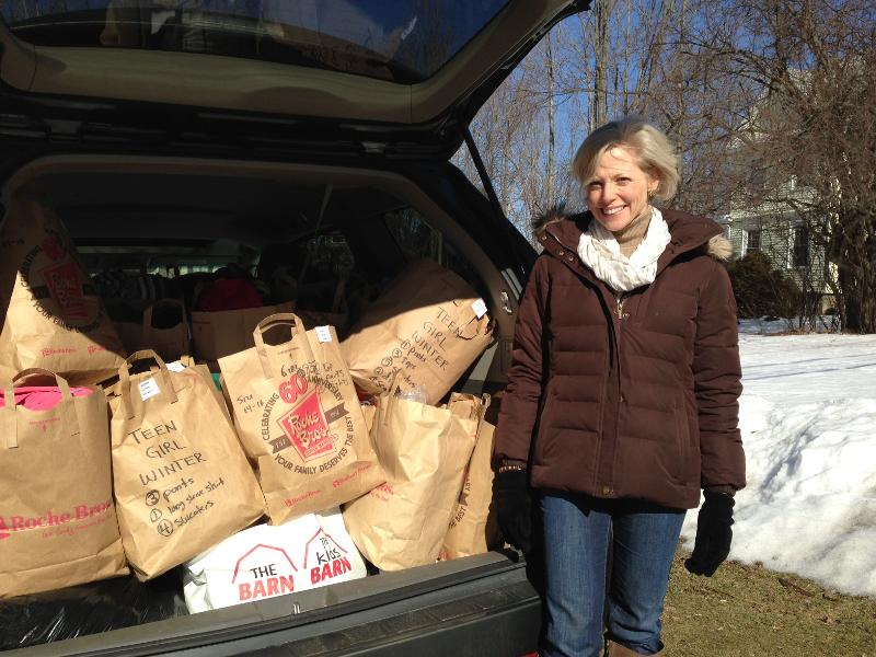 Circle of Hope volunteer stands next to a a car full of donation bags.