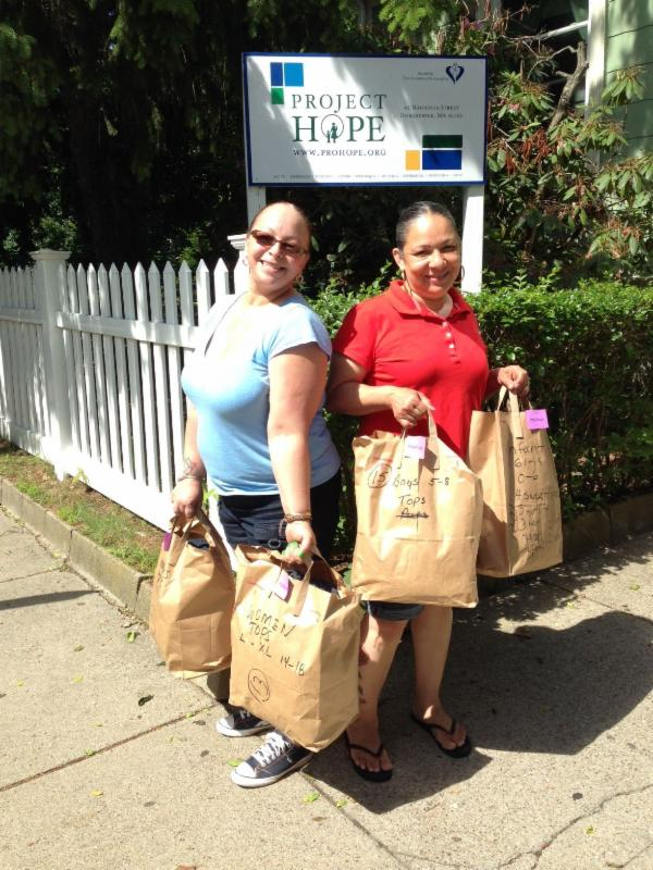 Two shelter staff members stand holding Circle of Hope donation bags full of clothing.