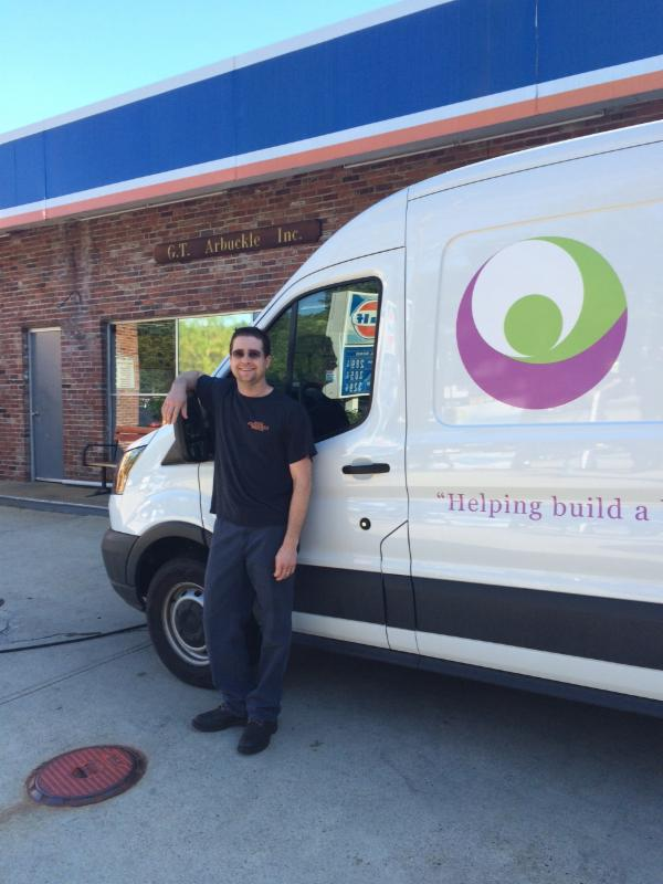 A man stands with the Circle of Hope delivery van.