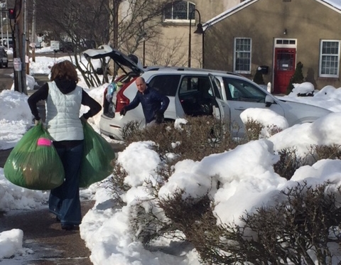Circle of Hope volunteers load bags into a car for an emergency winter delivery to a shelter.