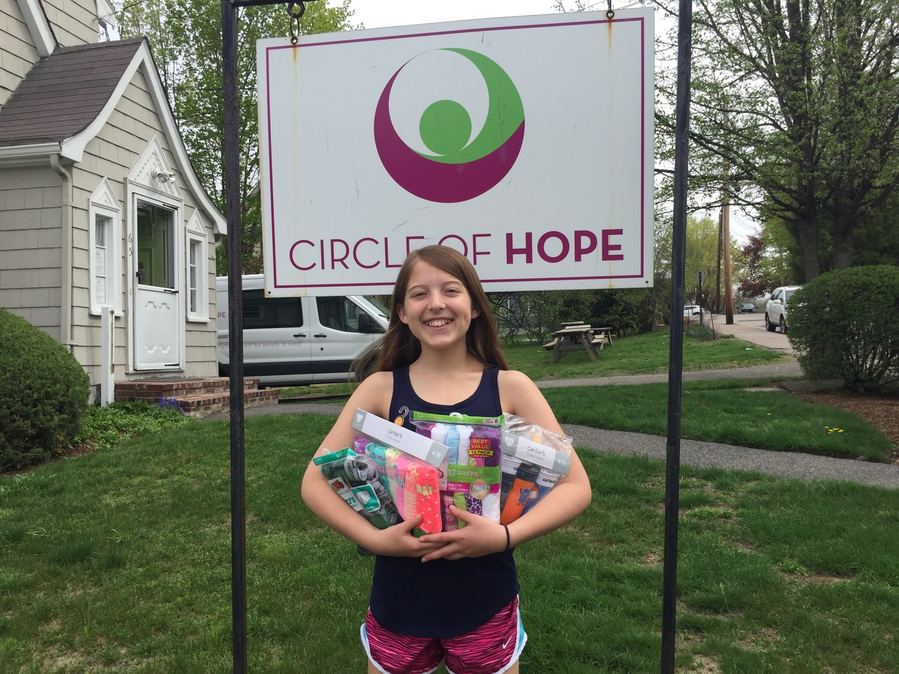 A young donor stands with donations in front of Circle of Hope sign