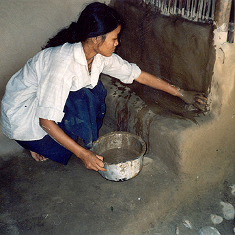 She is smearing her hut with mud.  This keeps it clean and tidy which is the only way to eradicate disease.  It also makes the hut more decorative. Bishnu Maya  / PhotoVoice / LWF