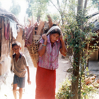A woman with a bundle of firewood on her back is selling it in the refugee camps. Refugees are not allowed to fetch firewood from the forest so they have to buy it- the brickettes provided are not sufficient for cooking. Til Maya / PhotoVoice / LWF