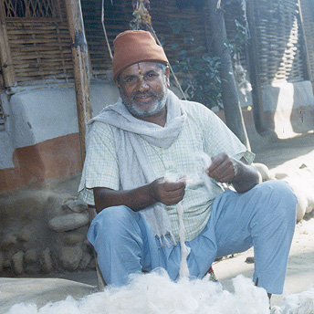 An old man works with wool to earn some money. He hopes that he will be able to return to Bhutan. Indra / PhotoVoice / LWF