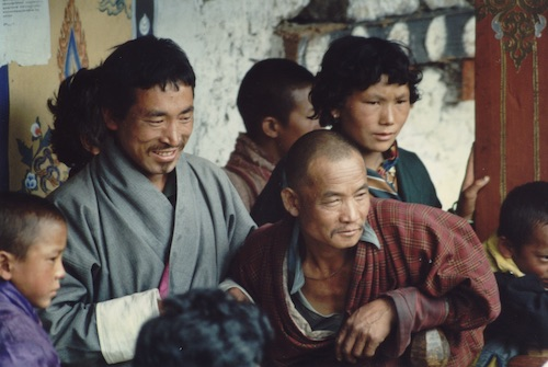 Bhutanese men watch a festival.