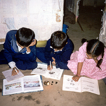 These students are trying to do their homework in their huts by the light of a small small flame. Students are compelled to finish their homework and study in the daytime because we are not provided with fuel for lighting.   Bhakta / PhotoVoice / LWF