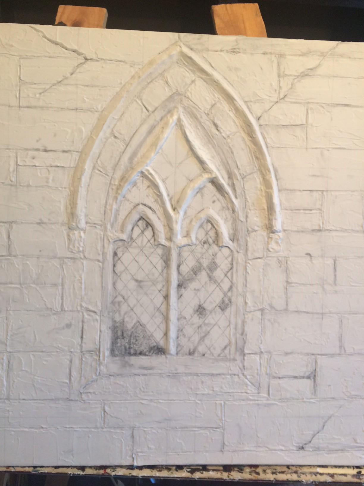 Continued adding modeling paste over entire canvas to represent texture of stone.