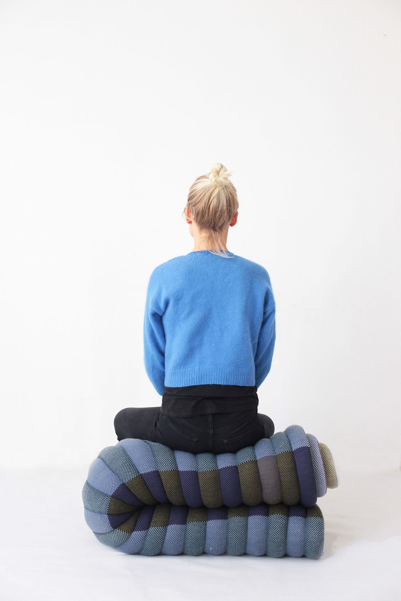 Oruga  is a module of 150 x 200 cm, constructed with filled bands, all knitted. It forms rhythmic combination of colours and uneven lines. It can be reshaped to seat, sleep, read, cover up or lie down. It's made to adapt actively to your body and find any kind of comfort on the floor with a warming touch. Made in Belgium.