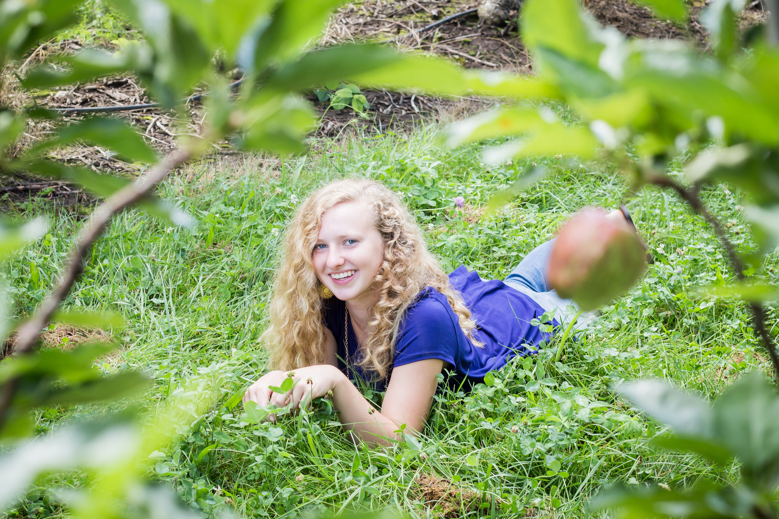 senior photos in Michigan apple orchard laying in grass