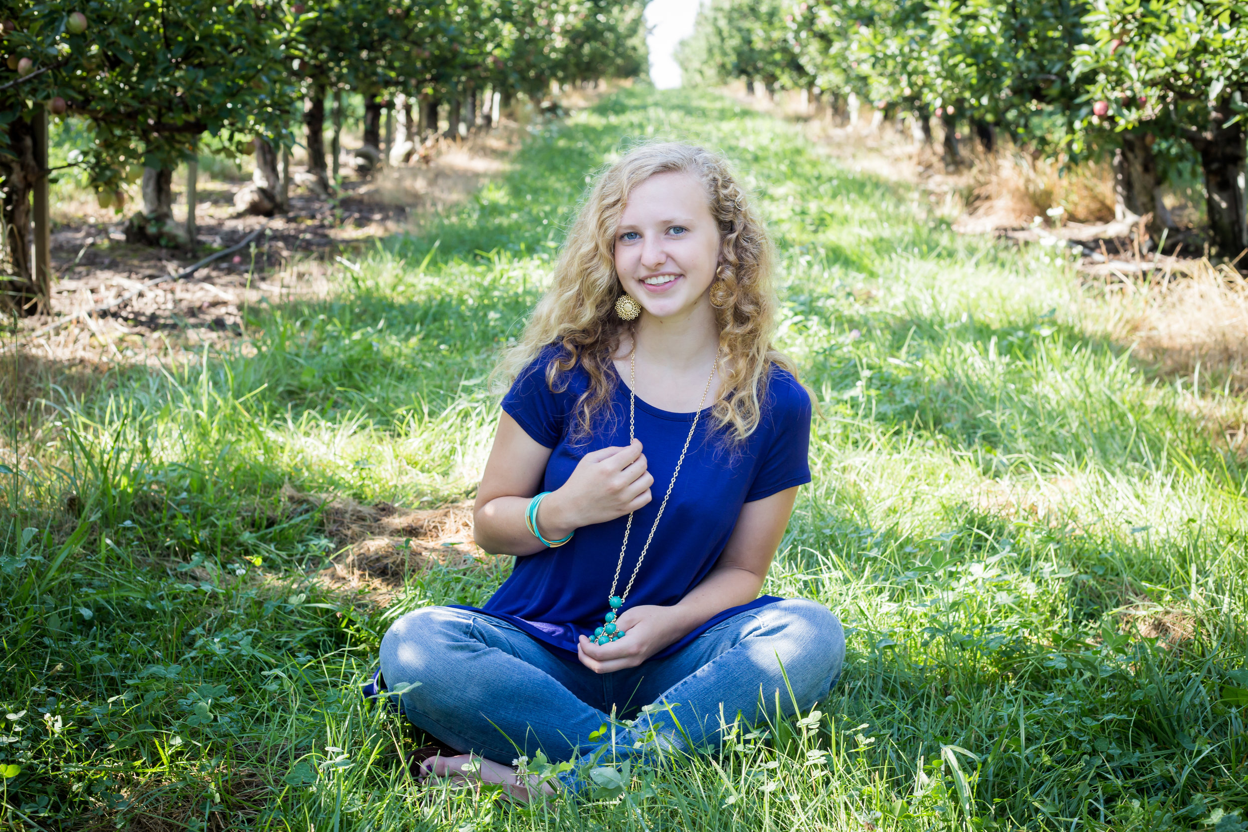 Sitting in apple orchard senior photos holding necklace Sparta Michigan