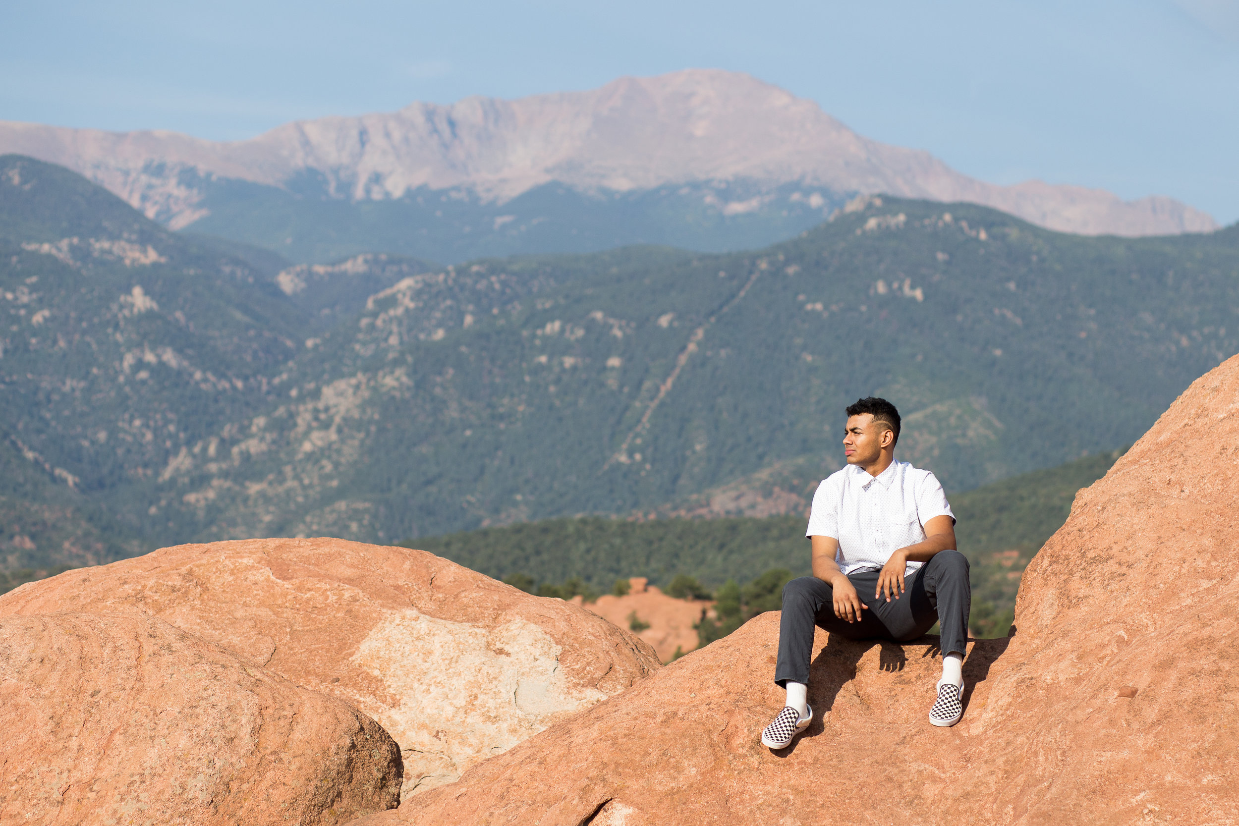 Stacy Carosa Photography Liberty High School Garden of the Gods you male sitting on red rocks in front of Pikes Peak