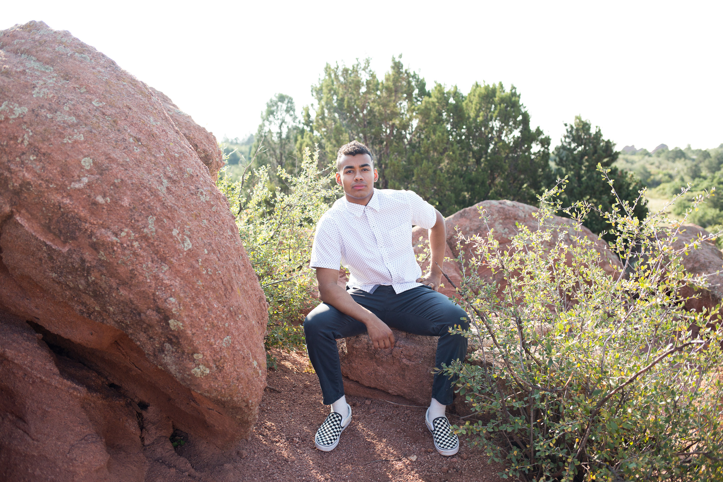 Stacy Carosa Photography senior boy sitting on red rock in Garden of the Gods by green bushes